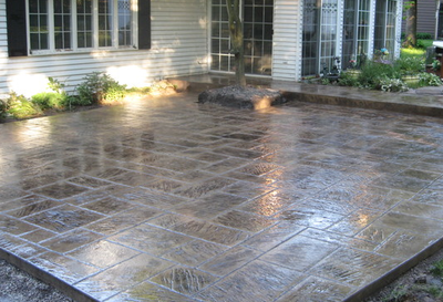 Polished dark gray stone shaped stamped patio.