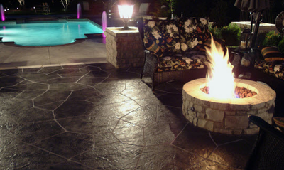 Dark brown multi-sized stone shaped stamped concrete patio.