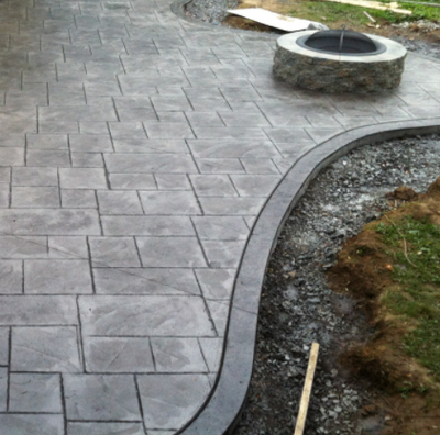 Stamped concrete colored gray and edged around front yard landscaping.