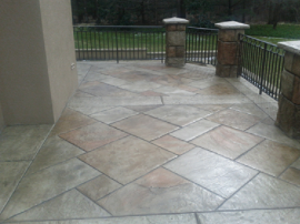Multi-brown colored stamped concrete around a large front porch.