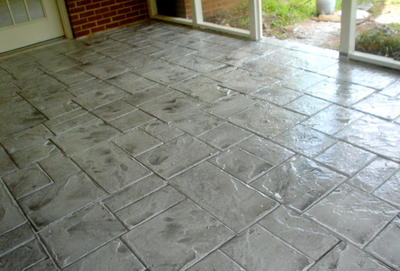 Polished gray stamped concrete indoor patio.