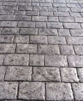 Dark gray stamped concrete made to resemble old weathered brick.